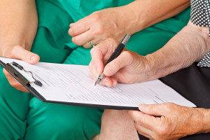 A senior woman's hand signing a document