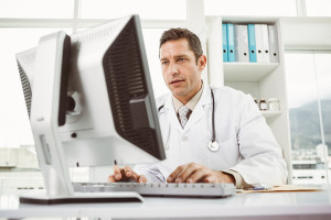 Concentrated male doctor using computer at the medical office